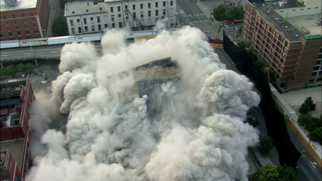 ws building in the middle of the city is demolished in controlled implosion using explosives creating huge dust cloud / louisvile, kentucky, usa - imploding stock videos and b-roll footage