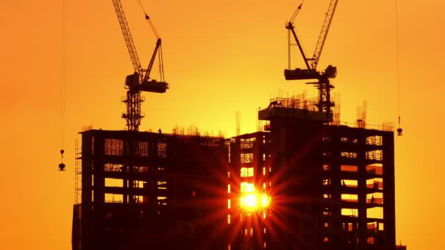 vidéos et rushes de bâtiment dans le processus de construction. dans la grue de travail de fond, forêt, mer et coucher du soleil. vidéo stock. - béton