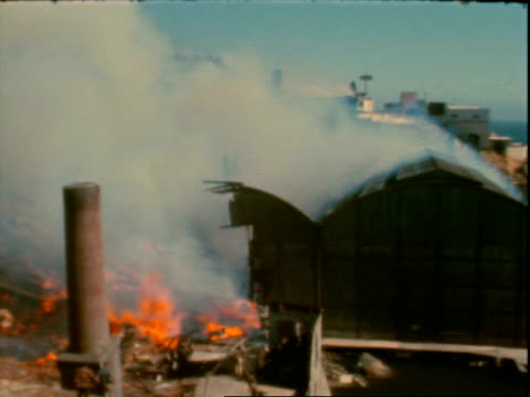 building on fire and smoke rising / firefighters / spectators on cliff watching / fire and smoke. warehouse fire on january 01, 1963 in california - warehouse点の映像素材/bロール