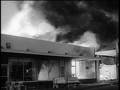 B/W 1965 building on fire during Watts race riots / Los Angeles / newsreel