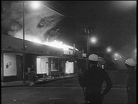 B/W 1965 building on fire during Watts race riots / policeman in foreground / Los Angeles / newsreel