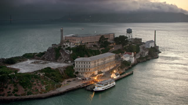 aerial building on the alcatraz island with their lights on at dusk - san francisco california video stock e b–roll