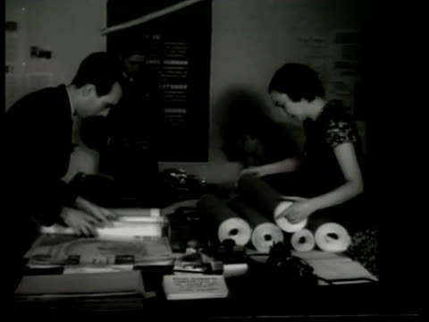 Building sign 'Accion Argentina' INT MS Accion members rolling up posters propaganda on table CU Propaganda poster being rolled up CU Pamphlet about...