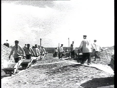 building sites w/ zeks / prisoners at work cu man digging mud wheelbarrows worksites in labour camps / gulags most probably from the propaganda... - 1937 stock-videos und b-roll-filmmaterial