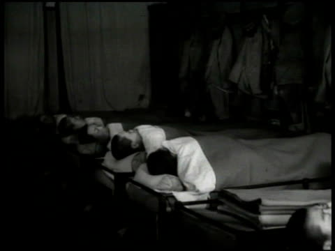 stockvideo's en b-roll-footage met building. two soldiers praying at ancestor shrine. soldiers sleeping in barracks. silhouette of japanese buglar. soldiers out of beds, dressing.... - 1936