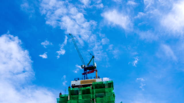 building under construction against blue sky - crane construction machinery stock videos & royalty-free footage