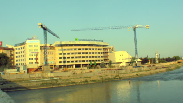 WS Building under construction, man fishing in foreground / Skopje, Macedonia
