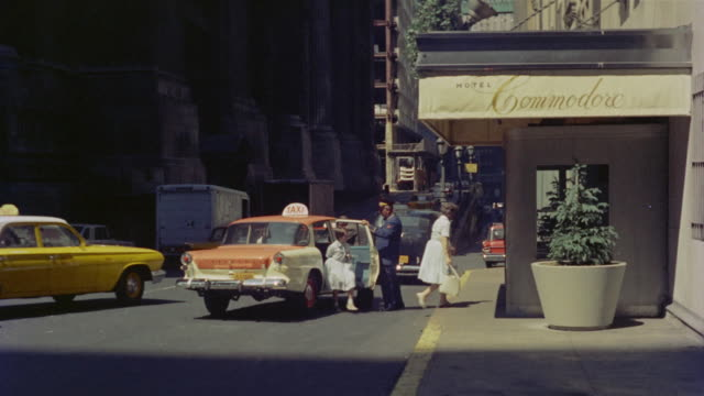 stockvideo's en b-roll-footage met 1958 ws la pan am building under construction / ws women getting out of taxi and entering hotel commodre / manhattan, new york - metlife building