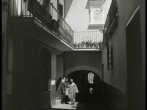building u.s. flag. sign 'consulate u.s.a.' men in robes walking in alley way balconies above. office man speaking w/ family at desk assistant.... - 1938 stock videos & royalty-free footage