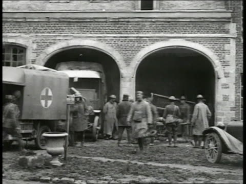 building w/ arched doors ambulances soldiers standing outside man being carried on stretcher ms us soldiers lifting wounded soldier out of truck on... - 1918 stock videos and b-roll footage