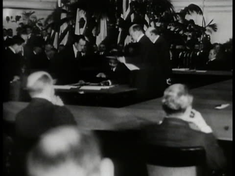 Building w/ people seated at large square table in gallery BG Unidentified Japanese male signing paper British Prime Minister Lord Balfour signing CU...