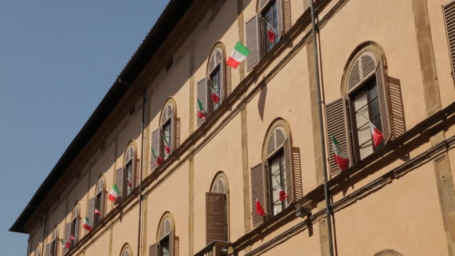 mh la td building with italian flags / tuscany, italy - italienische flagge stock-videos und b-roll-filmmaterial