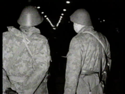 building work continues on the berlin wall on the east side / sign 'friedrichstrasse' pan to east german troops / us troops at checkpoint behind... - 1961 stock-videos und b-roll-filmmaterial