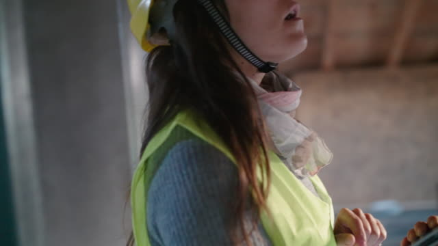 building your home. a confident female architect working on the roof structure on a construction site of a residential building on a bright sunny day. drywall structure. - quality control stock videos & royalty-free footage