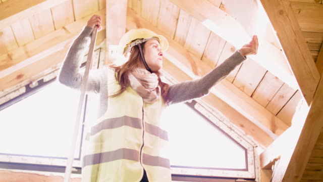 vidéos et rushes de construire votre maison. une architecte féminine confiante travaillant sur la structure de toit sur un chantier de construction d'un bâtiment résidentiel un jour ensoleillé lumineux. - charpente
