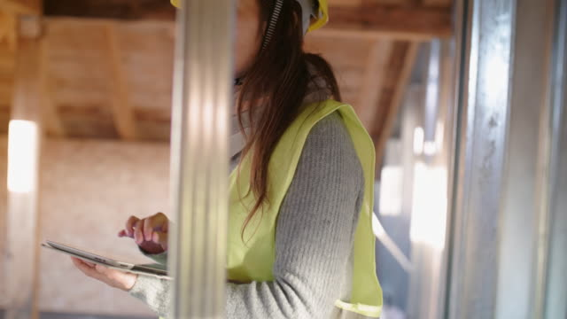 building your home. a confident female architect working on the roof structure on a construction site of a residential building on a bright sunny day. drywall structure. - females stock videos & royalty-free footage