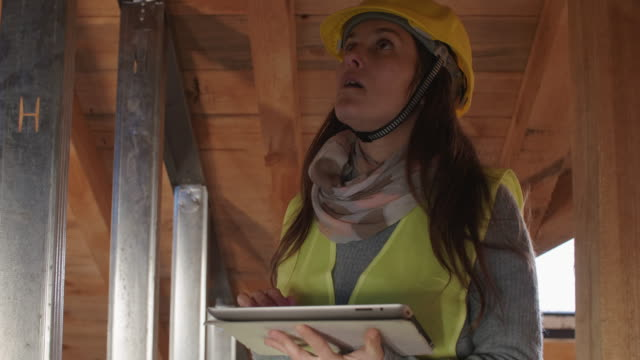 building your home. a confident female architect working on the roof structure on a construction site of a residential building on a bright sunny day. drywall structure. - inspector stock videos & royalty-free footage