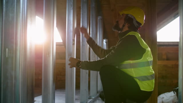 building your home. active seniors. an experienced engineer working at construction site of a residential building on a bright sunny day. building drywall structure. - plaster stock videos & royalty-free footage