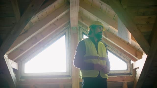 vídeos de stock, filmes e b-roll de construindo sua casa. idosos ativos. um coordenador experiente que trabalha no canteiro de obras de um edifício residencial em um dia ensolarado brilhante. construindo a estrutura de drywall. - só um homem maduro