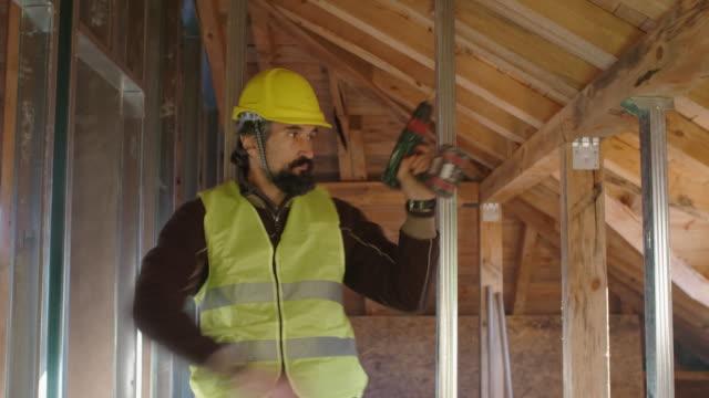 vidéos et rushes de construire votre maison. personnes âgées actives. un ingénieur expérimenté travaillant au chantier de construction d'un bâtiment résidentiel un jour ensoleillé lumineux. construire la structure drywall et faire des blagues tout en travaillant. de l - artisant