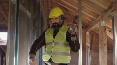 vidéos et rushes de construire votre maison. personnes âgées actives. un ingénieur expérimenté travaillant au chantier de construction d'un bâtiment résidentiel un jour ensoleillé lumineux. construire la structure drywall et faire des blagues tout en travaillant. de l - classe ouvrière