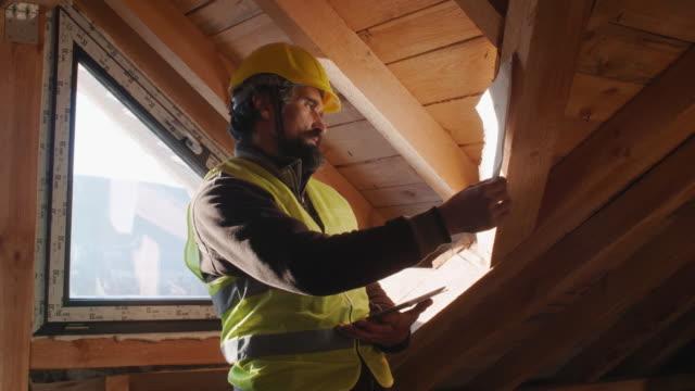 vidéos et rushes de construire votre maison. un ingénieur expérimenté travaillant au chantier de construction d'un bâtiment résidentiel un jour ensoleillé lumineux. - charpente