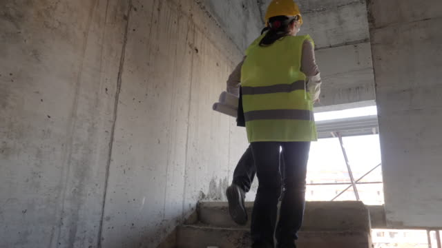 vídeos de stock, filmes e b-roll de construindo sua casa. reunião de um arquiteto fêmea confiável e de um trabalhador da construção que discutem e que trabalham junto no canteiro de obras de um edifício residencial em um dia ensolarado brilhante. - concrete
