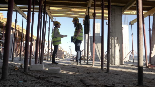 vídeos de stock e filmes b-roll de building your home. meeting of a confident female architect and a construction worker discussing and working together at construction site of a residential building on a bright sunny day. - andaime