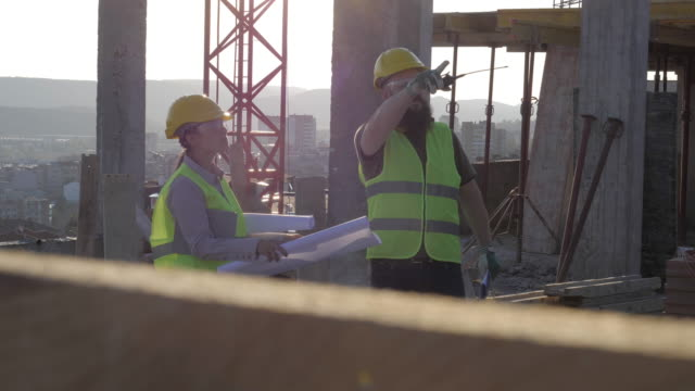 building your home. meeting of a confident female architect and a construction worker discussing and working together at construction site of a residential building on a bright sunny day. - concrete stock videos & royalty-free footage