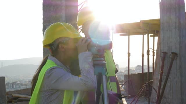 vídeos de stock, filmes e b-roll de construindo sua casa. reunião de um arquiteto fêmea confiável e de um geodesist que discutem e que trabalham junto no canteiro de obras de um edifício residencial em um dia ensolarado brilhante. - concrete