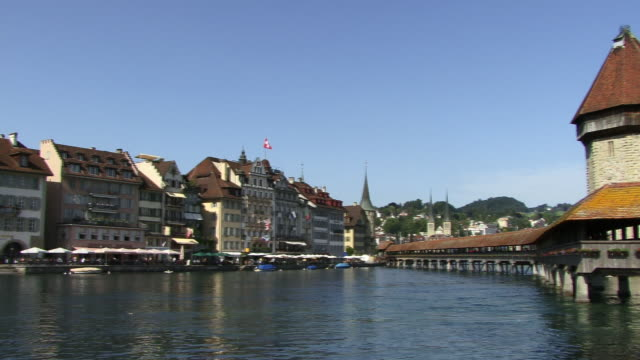 ms, pan, buildings along river reuss with chapel bridge and water tower, lucerne, switzerland - circa 14th century stock videos & royalty-free footage
