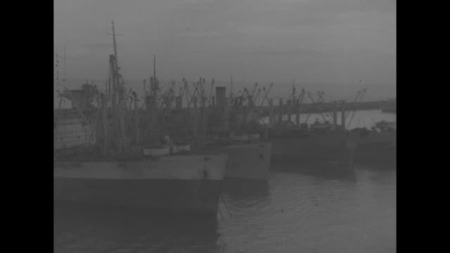 vs buildings alongside an unidentified harbor damaged ships american battleship ship with scores of sailors men carrying wooden crates sailors atop... - kriegsschiff stock-videos und b-roll-filmmaterial