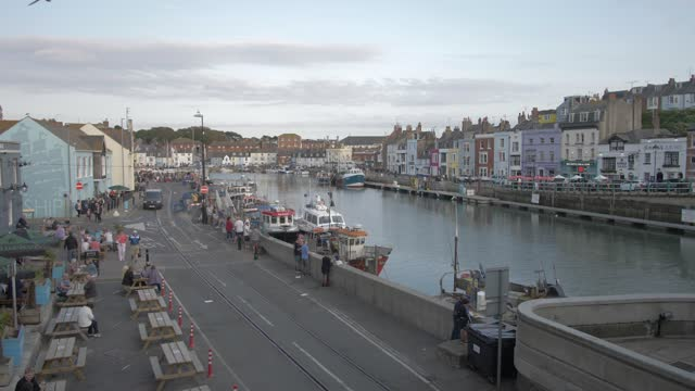 buildings and boats in harbour at sunset, weymouth, dorset, england, united kingdom, europe - ウィルトシャー州点の映像素材/bロール