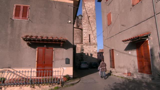 vídeos y material grabado en eventos de stock de buildings and tower in lucca, tuscany with two pedestrians - detalle arquitectónico exterior