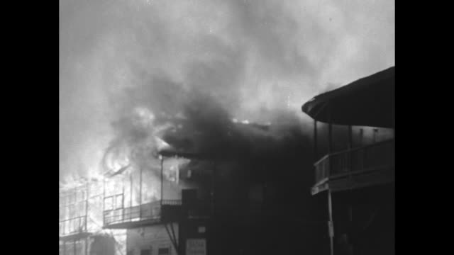 buildings burning at night / stream of water from fire hose hitting burning building / pan across burning buildings / three shots of burning... - colon stock videos and b-roll footage