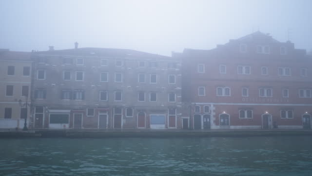 buildings by canal on foggy day seen from boat - nebbia video stock e b–roll