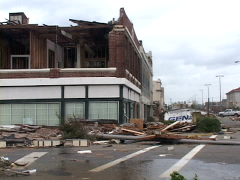 vidéos et rushes de a buildings facade collapses into the street in gulfport ms as a result of hurricane katrina's 140mph winds debris carried by storm surge litters the... - endommagé