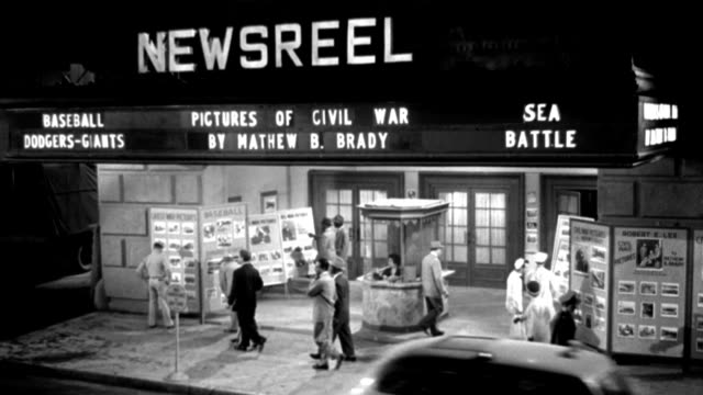 """dx - buildings - high m.l.s. exterior newsreel theater - on marquee:  """"pictures of civil war by matthew b. brady"""", """"sea battle"""", etc. - people seen - cars and taxi-cabs through l to r f.g. - b&w. (neg only) - newsreel stock videos & royalty-free footage"""