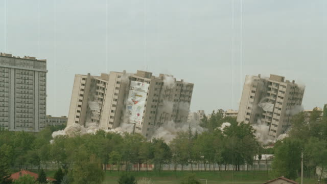 vidéos et rushes de buildings imploding and collapsing / demolition - imploding