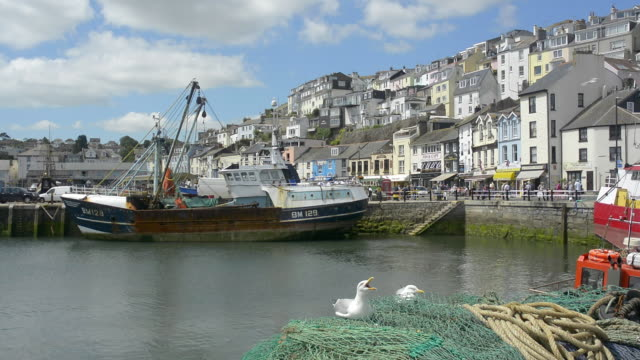stockvideo's en b-roll-footage met buildings in the town of brixham rise up above the fishing boats in the harbour. - devon