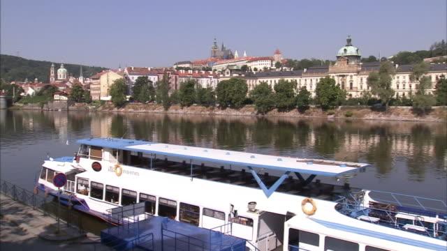 vídeos de stock e filmes b-roll de buildings line a canal near a docked tour boat. - barco de turismo