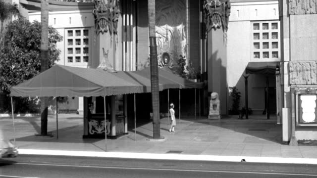 dx - buildings - l.s. top of the mann's chinese theater - hollywood - pan down to show court - a girl (mary thatcher's double) walks in from r f.g. to center by awning - looks about - a taxi-cab and a couple of cars through f.g. - b&w. - tcl chinese theatre stock videos & royalty-free footage