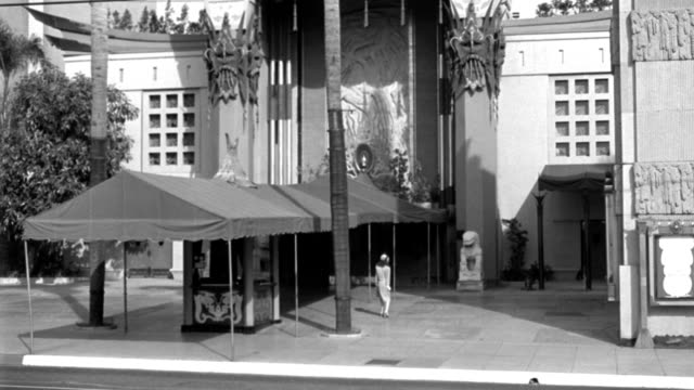dx - buildings - l.s. top of the mann's chinese theater - hollywood - pan down to show court - a girl (mary thatcher's double) makes entrance r f.g. - looks about - a taxi-cab and a couple of cars through f.g. - start to zoom toward the girl - b&w. - tcl chinese theatre stock videos & royalty-free footage