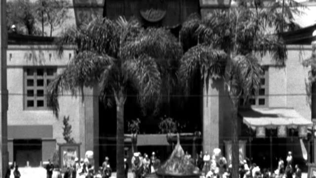 dx - buildings - m.s. pagoda top the mann's chinese theater - hollywood - pan down to fair crowd in court - b&w. - pagoda stock videos & royalty-free footage