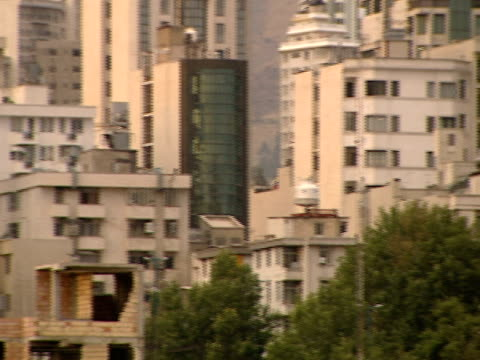 pan buildings of various heights and materials in the city with the alborz mountains beyond / tehran, tehran, iran - letterbox format stock videos & royalty-free footage