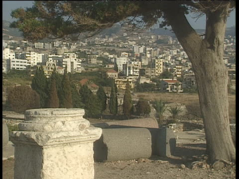 buildings on hillside framed by tree and broken columns lebanon - old ruin stock videos & royalty-free footage