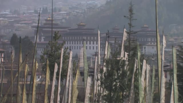 buildings on the hillsides in thimphu, the capital of bhutan, with prayer flags in the foreground. - thimphu stock videos & royalty-free footage