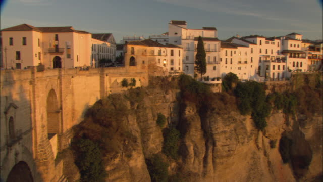 stockvideo's en b-roll-footage met ws pan buildings on top of cliff and old stone puente nuevo leading into town at sunset / ronda, andalusia, spain - puente