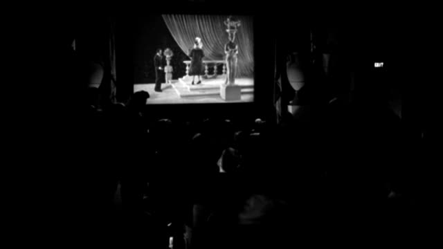 int - buildings - over audience toward screen newsreel theater - fashion show clip on screen- goes into paramount pictures news end title - b&w. (neg only) - newsreel stock videos & royalty-free footage