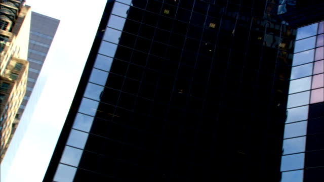 Buildings reflect in the windows of surrounding skyscrapers. Available in HD.